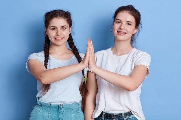 Dos hembras jóvenes morenas mostrando cinco