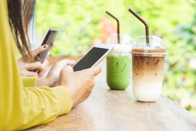 Dos hembras mano demandando teléfono inteligente en cafetería