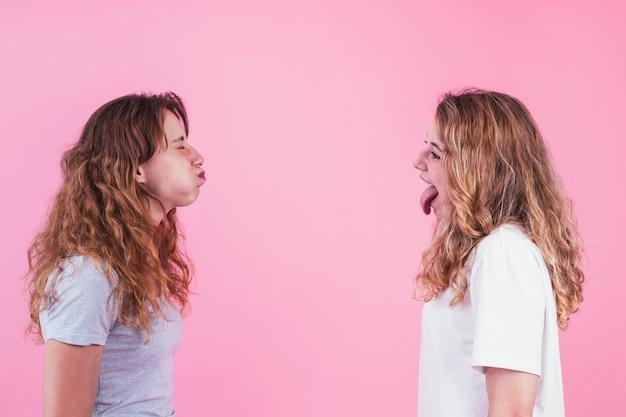 Dos hermana se burlan mutuamente contra fondo rosa