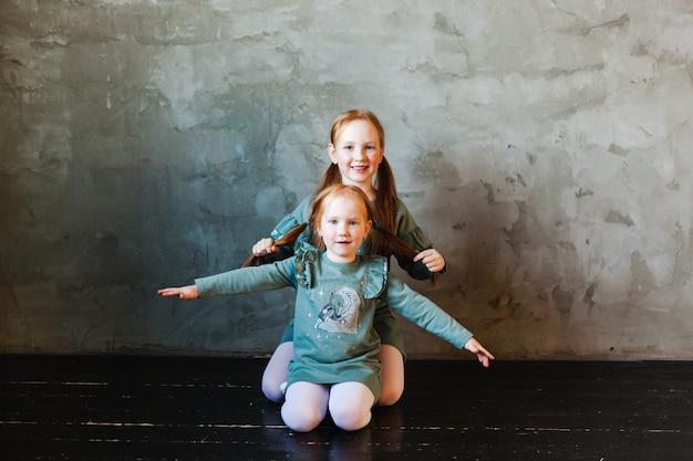 Dos hermanas abrazándose, cabello rojo, pecas, alegría, risas, familia