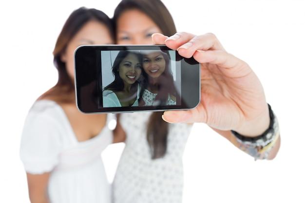 Dos hermanas asiáticas sonrientes que toman un autorretrato