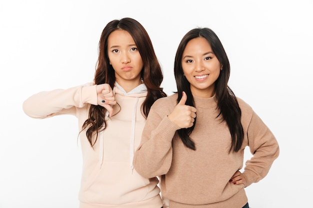 Dos hermanas bonitas asiáticas que muestran diferentes emociones