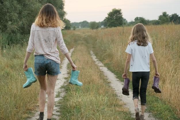Dos hermanas chicas felices caminando con botas de lluvia en las manos