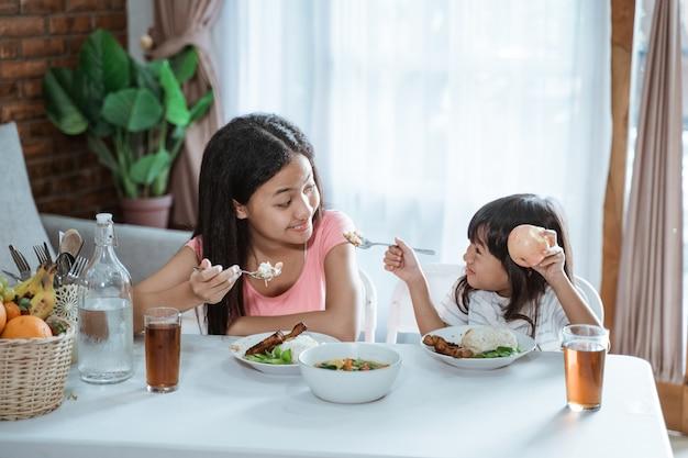 Dos hermanas disfrutan comiendo juntas en la mesa del comedor
