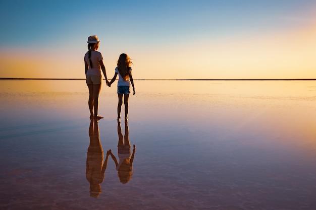 Dos hermanas encantadoras felices están caminando por el lago salado espejo disfrutando de la ardiente puesta de sol
