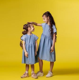 Dos hermanas están jugando. los niños miden el crecimiento entre ellos
