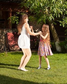 Dos hermanas de fiesta y bailando sobre el césped en el patio
