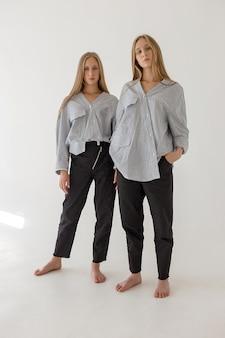 Dos hermanas gemelas bastante jóvenes con largo cabello rubio posando en la pared blanca en ropa de gran tamaño. sesión de fotos de moda