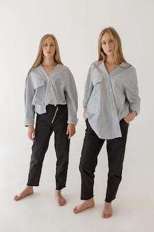 Dos hermanas gemelas bastante jóvenes con largo cabello rubio posando sobre fondo blanco en ropa de gran tamaño. sesión de fotos de moda