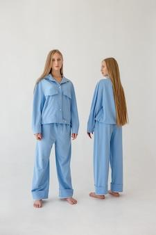 Dos hermanas gemelas con cabello largo posando en ropa de gran tamaño sobre fondo blanco.
