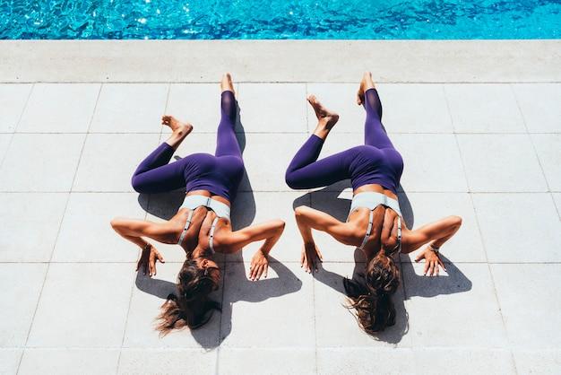 Dos hermanas gemelas femeninas haciendo ejercicio gimnástico junto a la piscina