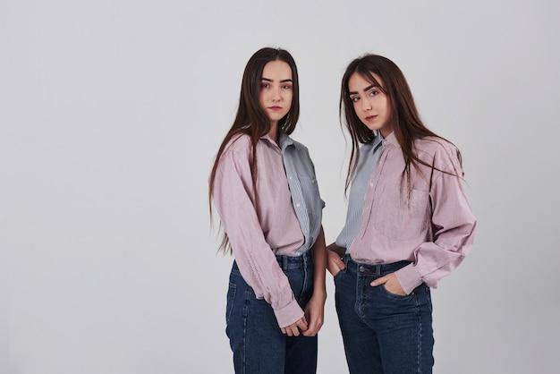 Dos hermanas gemelas de pie y posando en el estudio con fondo blanco.