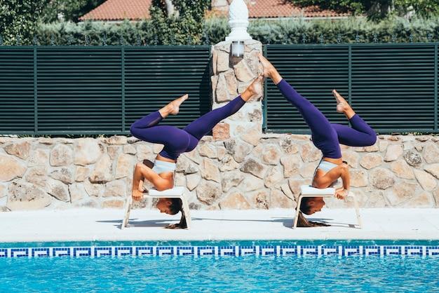 Dos hermanas gemelas practicando yoga en una piscina.