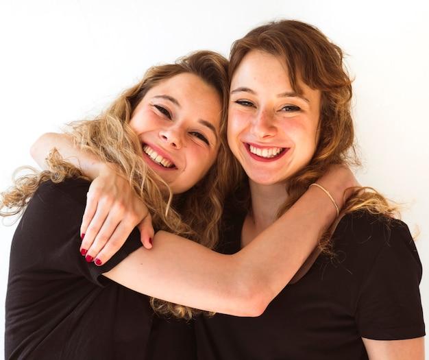 Dos hermanas jóvenes abrazándose contra el fondo blanco