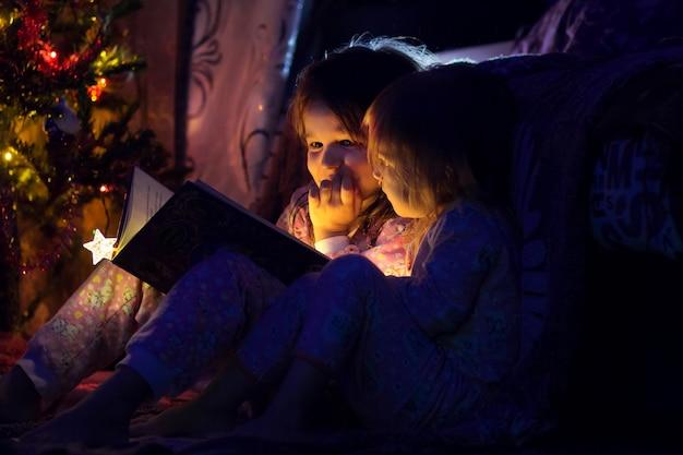 Dos hermanas leen el brillante libro cerca de un árbol de año nuevo.