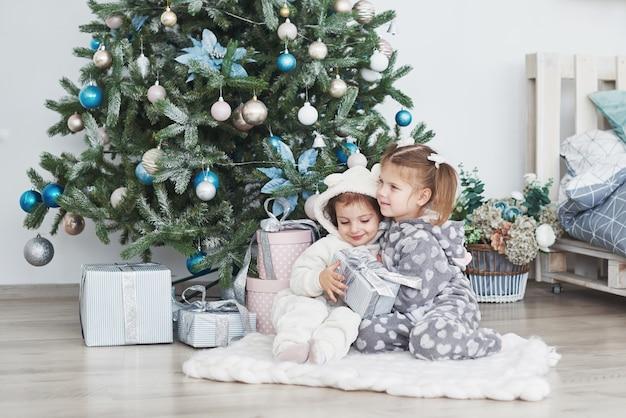 Dos hermanas pequeñas abren sus regalos en el árbol de navidad en la mañana