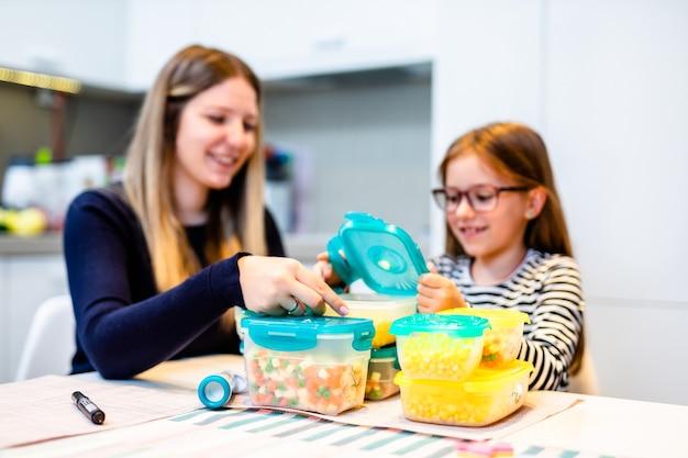 Dos hermanas que trabajan en la cocina de su casa y preparan verduras para el invierno en recipientes al vacío.