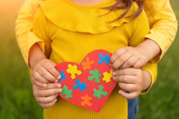 Dos hermanas sostienen un corazón rojo con coloridos rompecabezas en el interior hechos con sus propias manos