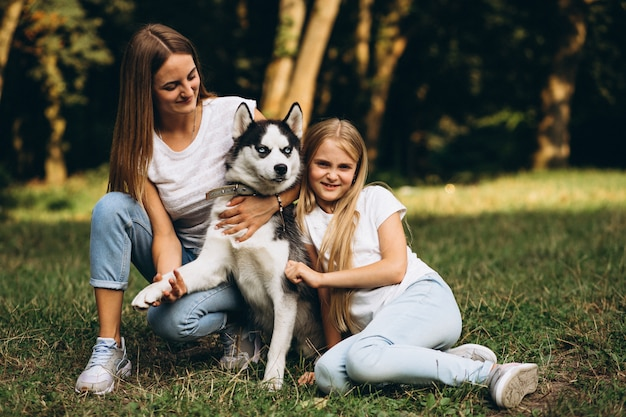 Dos hermanas con su perro en el parque.