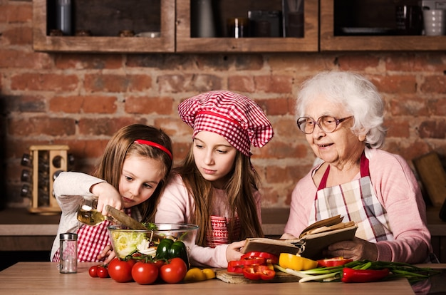 Dos hermanitas con abuelita cocinando juntas