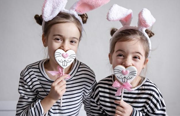 Dos hermanitas divertidas están posando con pan de jengibre de pascua en forma de caras de conejito.
