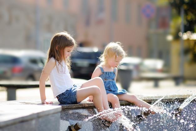 Dos hermanitas se divierten en una fuente de la ciudad en el caluroso día de verano