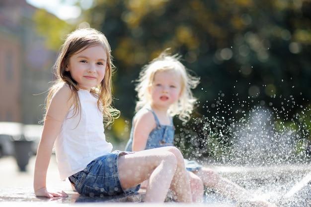 Dos hermanitas divirtiéndose en una fuente de la ciudad.