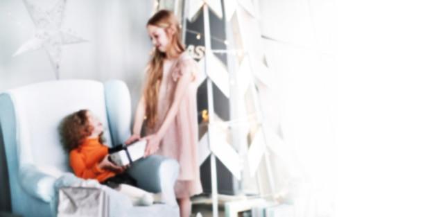 Dos hermanitas felices con regalos de navidad. imagen borrosa para el texto publicitario. foto con espacio de copia