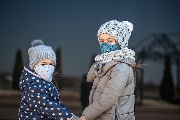 Dos hermanitas con máscaras y sombreros reutilizables durante el período de cuarentena sobre un fondo oscuro.