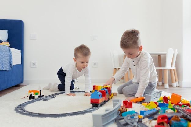 Dos hermanitos se divierten en su guardería, juegan al constructor y entrenan
