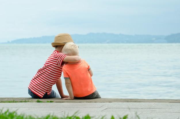 Dos hermanitos se sientan en un muelle y se abrazan contra el mar y las montañas a lo lejos