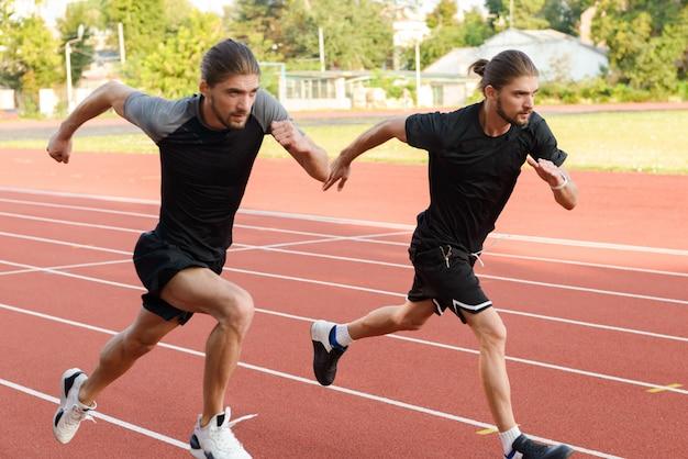 Dos hermanos gemelos deportistas corriendo en el estadio al aire libre.