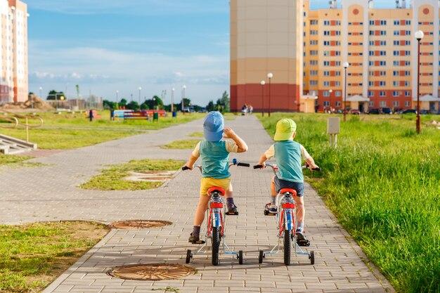 Dos hermanos gemelos montando bicicletas juntos