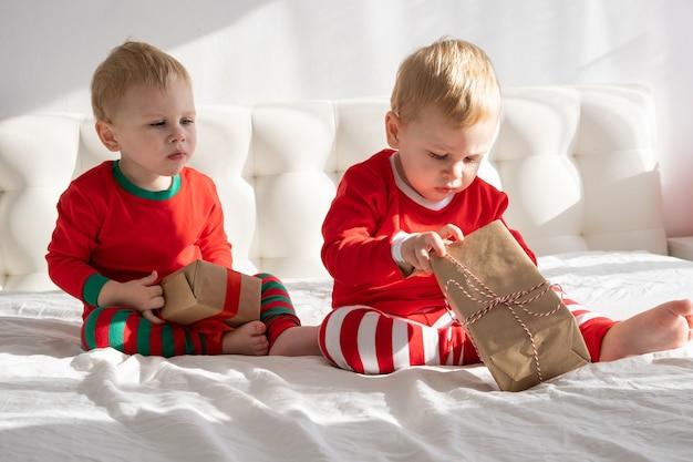Dos hermanos gemelos en trajes rojos abriendo la caja de regalo de navidad en la cama blanca en casa.