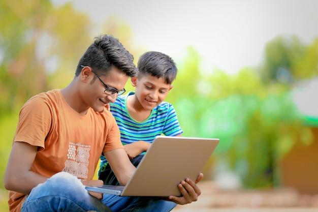 Dos hermanos indios que trabajan en la computadora portátil