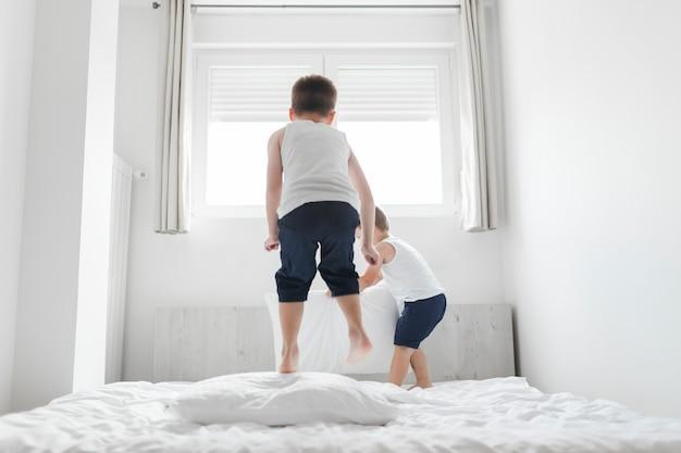 Dos hermanos jugando en la cama