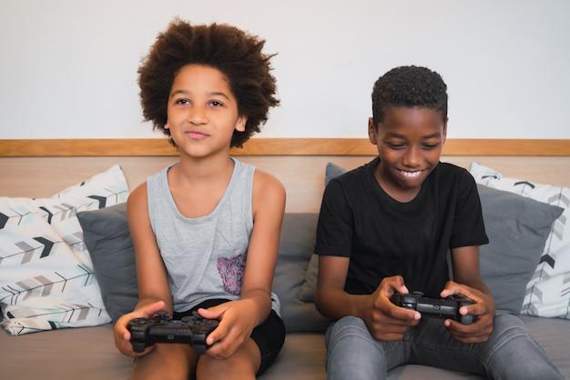 Dos hermanos jugando videojuegos en casa.