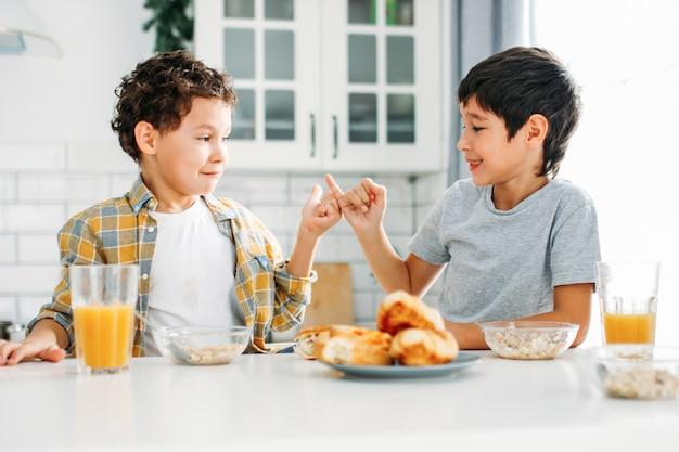 Dos hermanos entre los niños hermanos reales desayunando en la cocina brillante en casa