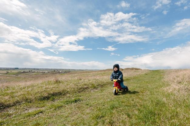 Dos hermanos pequeños activos divirtiéndose en bicicleta en las montañas en un día frío.