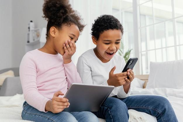 Dos hermanos sonrientes en casa juntos jugando en tableta y teléfono inteligente