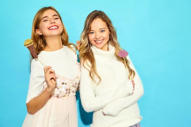 Dos hermosa joven cantando con accesorios de micrófono falso. mujeres de moda en ropa casual de verano. modelos divertidos aislados en la pared azul