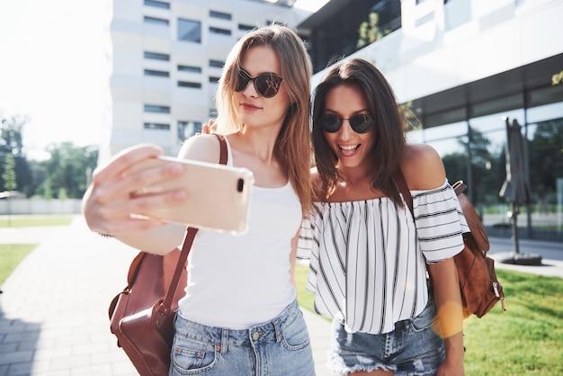 Dos hermosa joven estudiante feliz con mochila cerca del campus de la universidad y hacen una foto selfie. concepto de educación y ocio