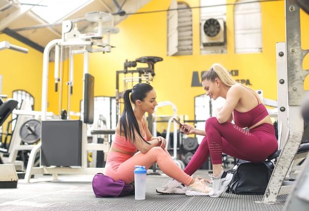 Dos hermosa mujer entrenando juntos en el gimnasio