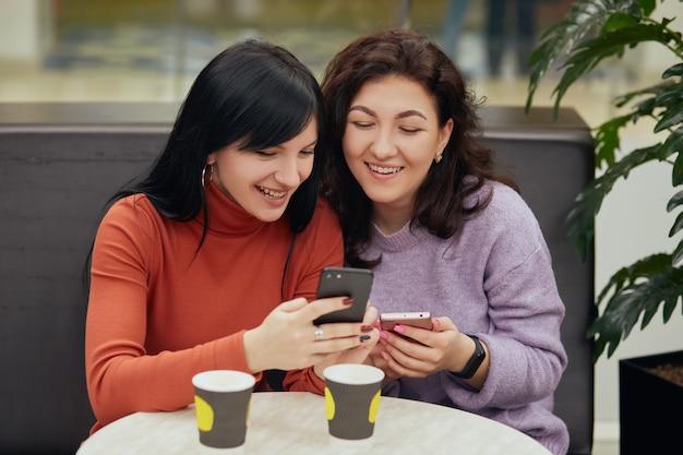 Dos hermosa mujer joven sentada en la cafetería tomando café y mirando el teléfono móvil, se ven felices, disfrutando de pasar tiempo juntos, damas con expresión positiva.
