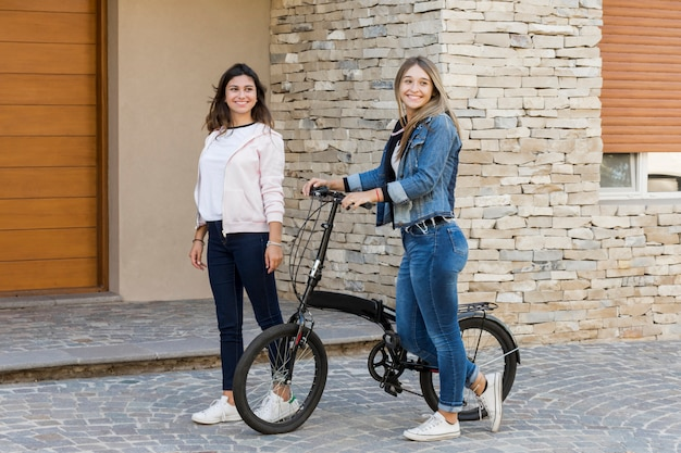 Dos hermosas amigas caminando fuera de la casa en bicicleta