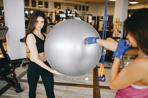 Dos hermosas chicas atléticas se dedican al gimnasio.