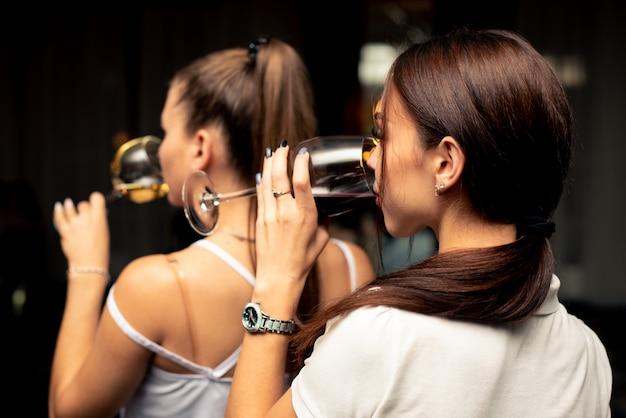 Dos hermosas chicas en blusas blancas beben vino de copas