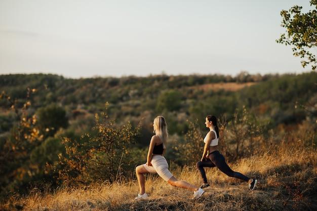 Dos hermosas chicas se dedican a hacer ejercicio en las montañas.