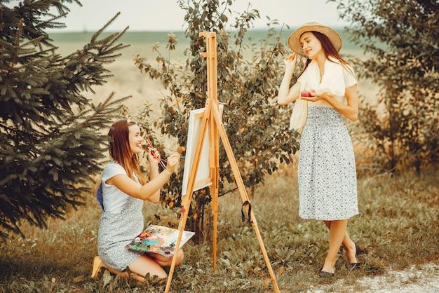 Dos hermosas chicas dibujando en un campo