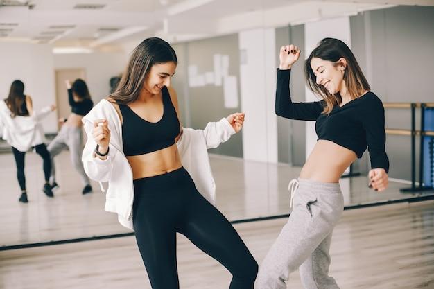 Dos hermosas chicas esbeltas haciendo baile y gimnasia en el salón de baile